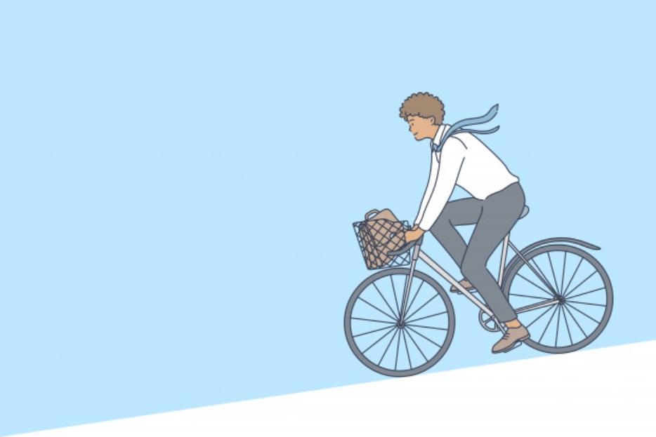 自転車で坂道を下る男性ビジネスマン